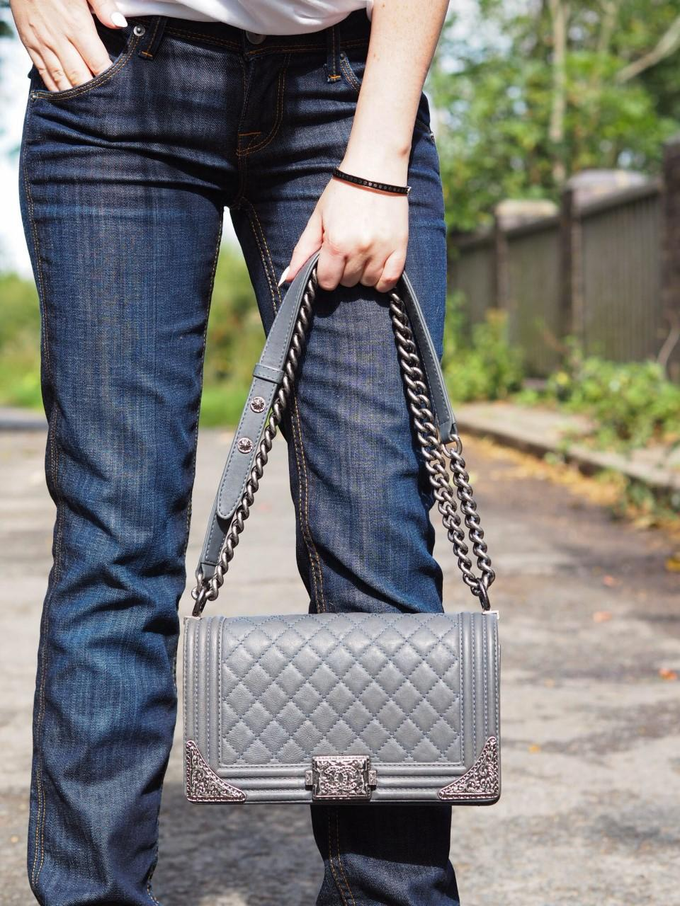 outfit photo of dark blue jeans and grey Chanel boy bag