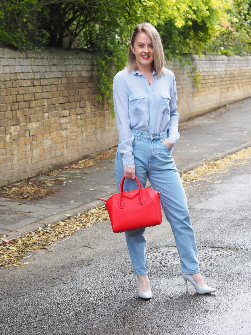 outfit photo of light blue silk shirt, mid blue jeans, pale blue court shoes and red Givenchy Antigona bag